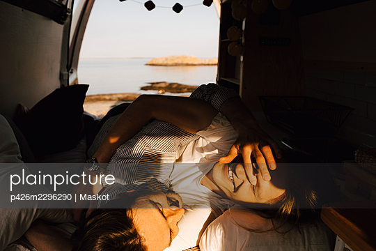 Gay couple relaxing at motor home during summer vacation - p426m2296290 by Maskot