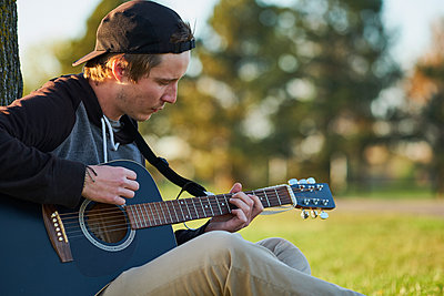 Young musician outside playing guitar in park - p1362m1553700 by Charles Knox