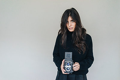 Dark-haired young woman holding vintage camera - p300m1449452 by Kniel Synnatzschke