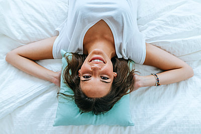 Top view of happy young woman lying in bed - p300m2132033 by Kiko Jimenez