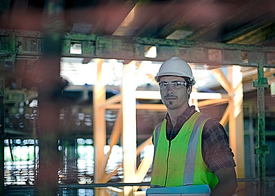 Confident male construction worker at construction site - p300m2250235 by LOUIS CHRISTIAN