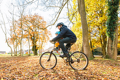 Caucasian father and son riding bicycle - p555m1472904 by Kolostock