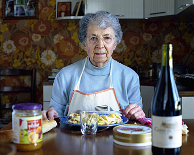 Senior woman eating at table, portrait - p6751827 by Jerome Gorin