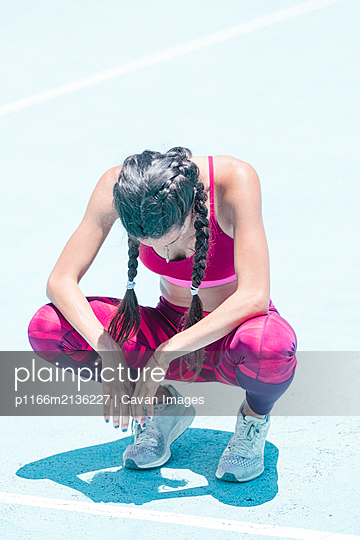 Colorful image of full body of female athlete resting on court - p1166m2136227 by Cavan Images