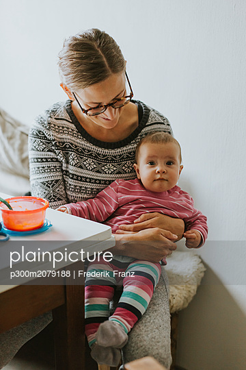 Smiling mother with baby at home - p300m2079188 by Frederik Franz