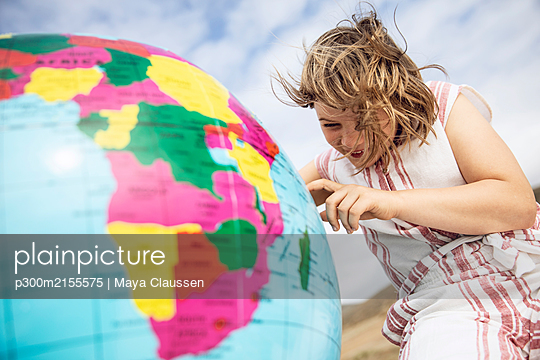 Little girl pointing on inflatable globe - p300m2155575 by Maya Claussen