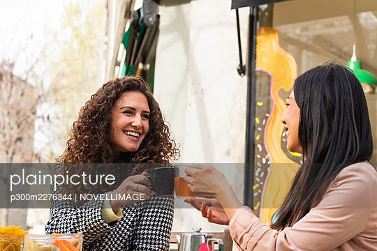 Smiling women toasting drink at sidewalk cafe - p300m2276344 by NOVELLIMAGE