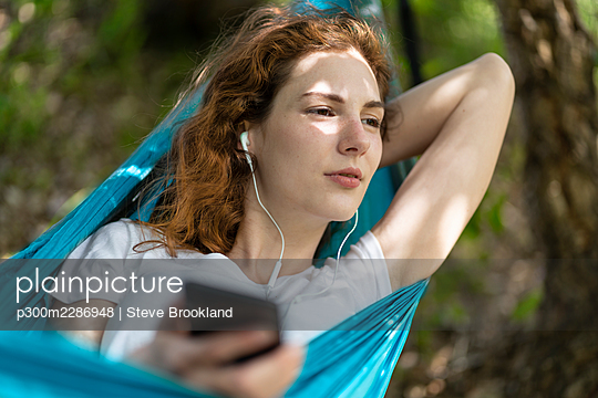 Thoughtful woman listening music while relaxing on hammock - p300m2286948 by Steve Brookland