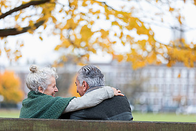 Carefree, affectionate senior couple hugging on bench in autumn park - p1023m2187623 by Tom Merton