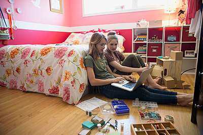 Girls using laptop making jewelry on bedroom floor - p1192m1158036 by Hero Images