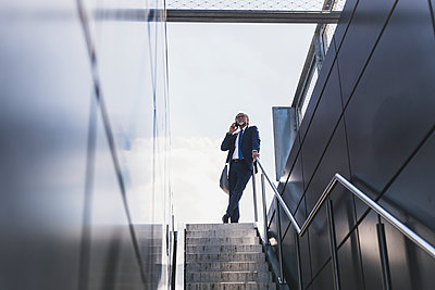 Smiling mature businessman at staircase in the city on cell phone - p300m1587574 by Uwe Umstätter