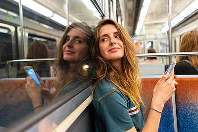 Portrait of smiling young woman and her mirror image in underground train - p300m2012293 von VITTA GALLERY