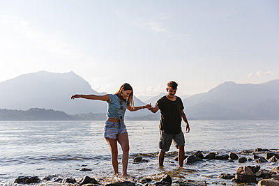 Young couple walking hand in hand at the lakeside - p300m2042933 von Michela Ravasio