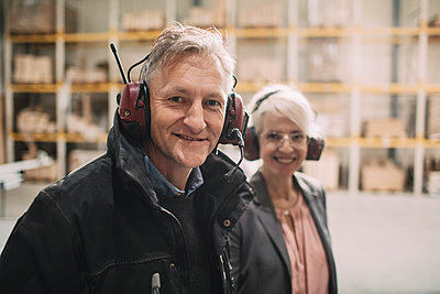 Portrait of smiling businessman with colleague wearing ear protectors at industry - p426m1537000 by Maskot