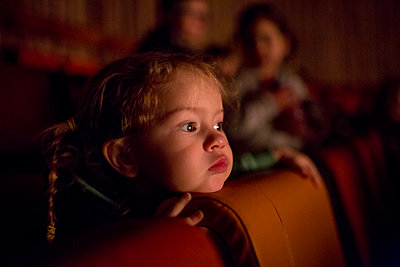 Caucasian girl watching movie in theater - p555m1482103 by Adam Hester