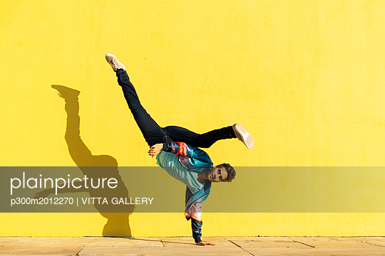 Acrobat doing movement training in front of a yellow wall - p300m2012270 von VITTA GALLERY