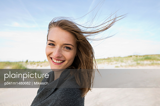 Young woman on beach with its dunes - p341m1480682 by Mikesch