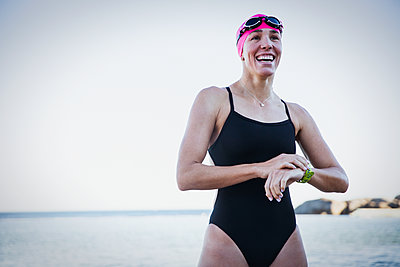 Smiling female open water swimmer adjusting smart watch at ocean - p1023m1520024 by Sam Edwards