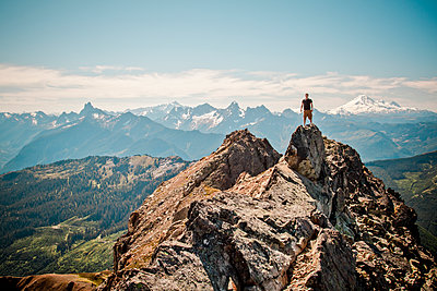 Hiker stands on summit of mountain with scenic view behind. - p1166m2269411 by Cavan Images