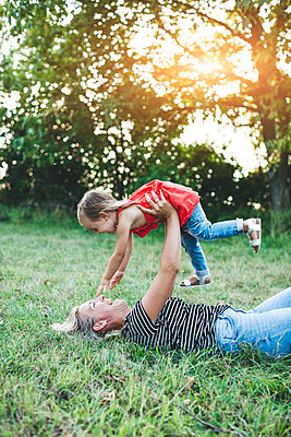 Happy mother playing with daughter on meadow - p300m2058873 by Epiximages