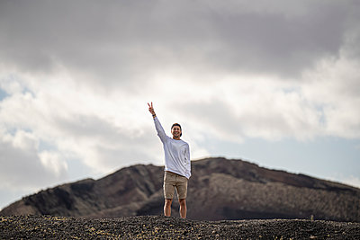 Caucasian male tourist peace gesturing while standing at el cuervo volcano - p300m2276611 by SERGIO NIEVAS