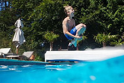 Boy jumping into swimming pool - p429m757633f by Zak Kendal
