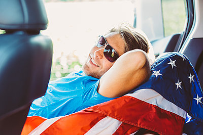Caucasian man laying on American flag in car - p555m1412578 by Inti St Clair