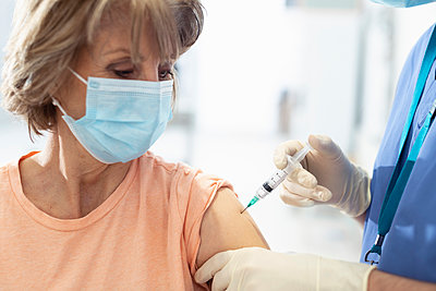 Older woman receiving Covid-19 vaccination - p924m2252562 by Monty Rakusen
