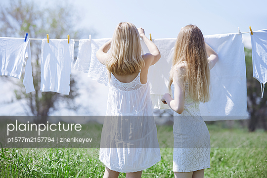 Two young blond women outdoors standing next to the drying linen - p1577m2157794 by zhenikeyev