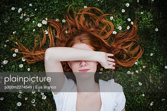 Redhead woman covering eyes while lying on grass - p300m2274549 by Eva Blanco