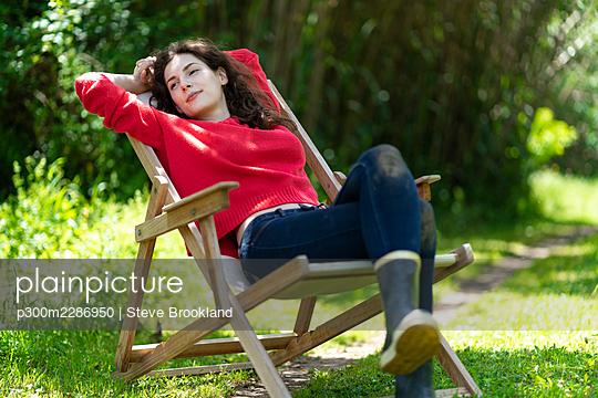 Woman relaxing in garden chair in sunny garden in Portugal - p300m2286950 von Steve Brookland