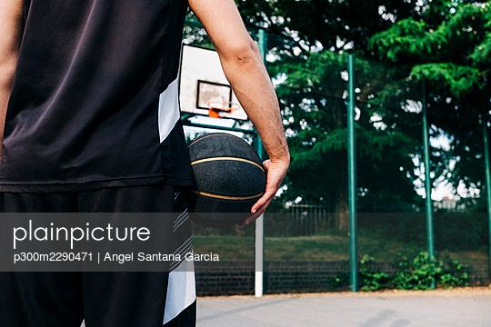 Athlete holding basketball at sports court - p300m2290471 by Angel Santana Garcia