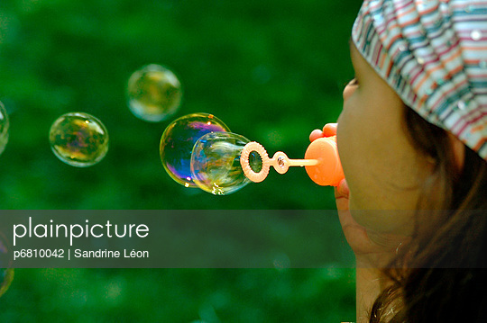 Little girl making soap bubbles - p6810042 by Sandrine Léon