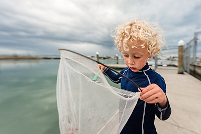 Young child looking in a net near the ocean - p1166m2124099 by Cavan Images