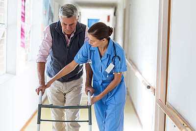 Nurse helping senior patient to walk with walking frame - p1315m1167733 by Wavebreak