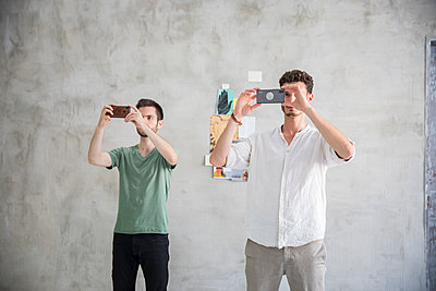 Two young men are taking pictures synchronous  - p276m2110758 by plainpicture