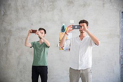 Zwei junge Männer fotografieren synchron mit dem Smartphone  - p276m2110758 von plainpicture