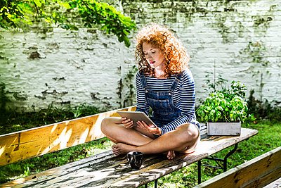 Portrait of young woman sitting on beer table in the garden using tablet - p300m2029014 by Jo Kirchherr
