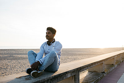 Thoughtful man sitting on retaining wall at beach against clear sky during sunny day - p300m2266628 by Josep Rovirosa