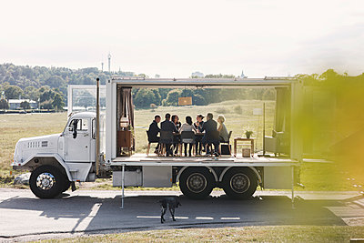 Business team working in portable office truck on road - p426m1442602 by Maskot