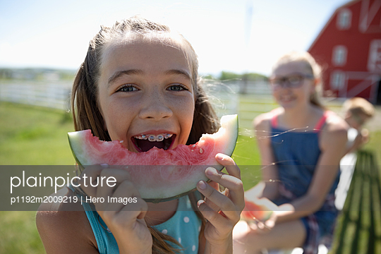 Portrait playful girl with braces eating watermelon on sunny farm - p1192m2009219 by Hero Images