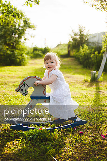 Little girl riding a rocking horse in the garden - p1642m2222254 by V-fokuse