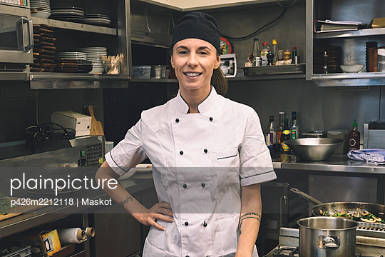 Portrait of smiling female chef with hand on hip in commercial kitchen - p426m2212118 by Maskot