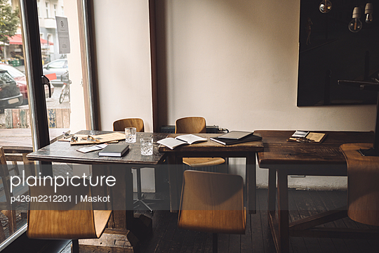 Empty chairs with diary on table in restaurant - p426m2212201 by Maskot