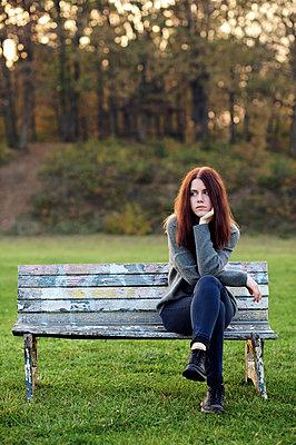Junge Frau auf einer Parkbank - p1412m2132885 von Svetlana Shemeleva