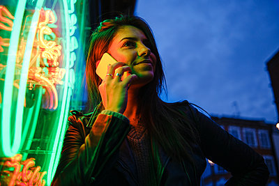 Smiling woman using mobile phone by standing illuminated light - p300m2273706 by Angel Santana Garcia