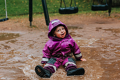Toddler girl sitting in puddle - p312m2239415 by Jennifer Nilsson