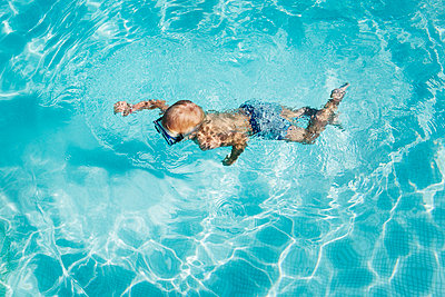 Boy swimming in pool - p352m2121022 by Folio Images