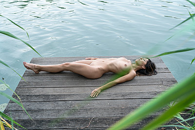 Naked woman lying on the waterfront - p427m2004883 by Ralf Mohr