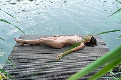 Nackte Frau liegt am Seeufer - p427m2004883 von R. Mohr